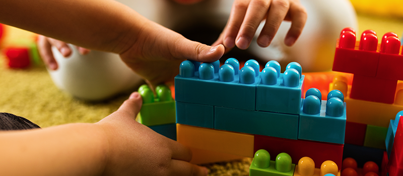 Two children playing with colorful building blocks.
